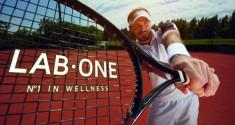 Racket in tennis player's hand on tennis court